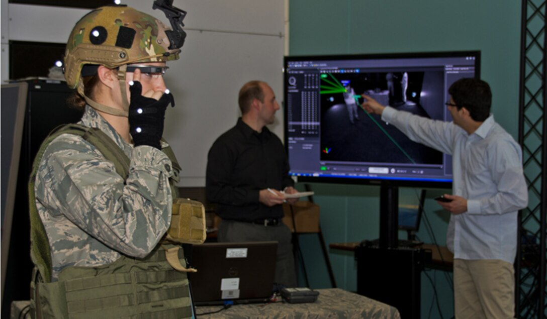 Dr. Gregory Burnett (middle) and Andres Calvo (right) analyze a graphic representation of movement trackers, as 2nd Lt. Krystin Shanklin tests Google Glass at Wright-Patterson Air Force Base, Ohio. Burnett is the chief engineer of the Battlefield Air Targeting, Man-Aided Knowledge, or BATMA(N) group, an advanced technology demonstration and research program at the 711 Human Performance Wing at the Air Force Research Laboratory. The team investigates emerging technologies, such as Google Glass' transparent, heads-up display, for possible military application. Calvo is a software developer and civilian contractor with the Wing. (U.S. Air Force photo/ Richard Eldridge)