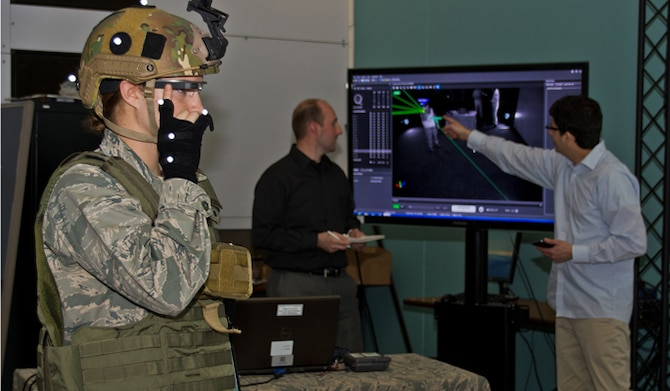 Dr. Gregory Burnett, middle, and Andres Calvo, right, analyze a graphic representation of movement trackers, as 2nd Lt. Krystin Shanklin tests Google Glass at Wright-Patterson Air Force Base, Ohio. Burnett is the chief engineer of the Battlefield Air Targeting, Man-Aided Knowledge, or BATMA(N) group, an advanced technology demonstration and research program at the 711 Human Performance Wing at the Air Force Research Laboratory. The team investigates emerging technologies, such as Google Glass' transparent, heads-up display, for possible military application. Calvo is a software developer and civilian contractor with the Wing. (U.S. Air Force photo/ Richard Eldridge)