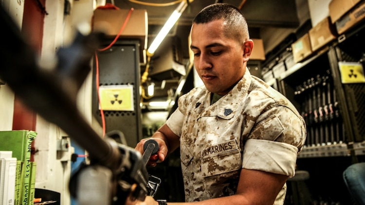 Sergeant Sigilfredo Garcia, small-arms technician, 15th Marine Expeditionary Unit, disassembles an M240B machine gun aboard Camp Pendleton, Calif., April 11, 2014. Garcia, 26, is from Watsonville, Calif. (U.S. Marine Corps photo by Cpl. Emmanuel Ramos/Released)