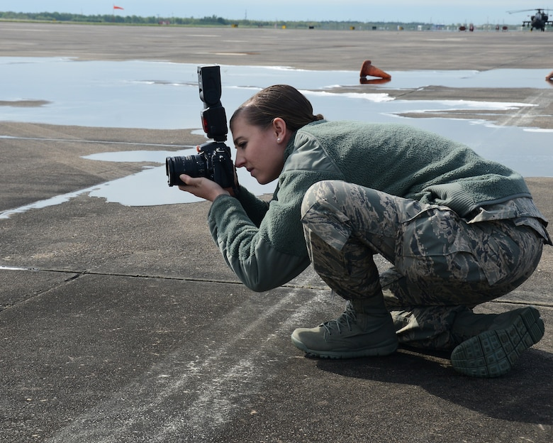 Senior Airman Chasity Lollis, 147th Reconnaissance Wing Public Affairs, squats down to shoot from a low perspective while photographing fire fighters extinguishing a simulated aircraft fire at Ellington Field Joint Reserve Base, April 5, 2014. The 147th Reconnaissance Wing participated in an Operational Readiness Exercise to test the wing's wartime readiness.