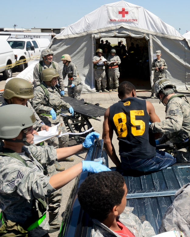Members of the 147th Medical Group unload victims of a simulated mass casualty event April 4, 2014 at Ellington Field Joint Reserve Base, Houston, TX. The mass casualty scenario was part of an Operational Readiness Exercise that tested the 147th Reconnaissance Wing's readiness and efficiency to respond to real world events.