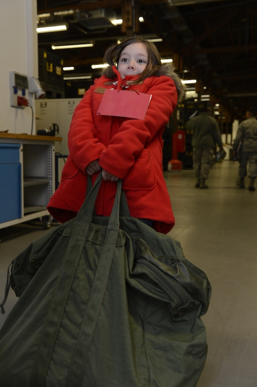 Elizabeth Faraone, daughter of U.S. Air Force Capt. Joseph Faraone, 606th Air Control Squadron, attempts to lift a fully packed mobility bag during Kids' Deployment Day at Spangdahlem Air Base, Germany, April 15, 2014. Spangdahlem Airmen invited students from the Bitburg and Spangdahlem Elementary Schools to experience what their parents go through during a deployment. (U.S. Air Force photo by Staff Sgt. Christopher Ruano/Released)