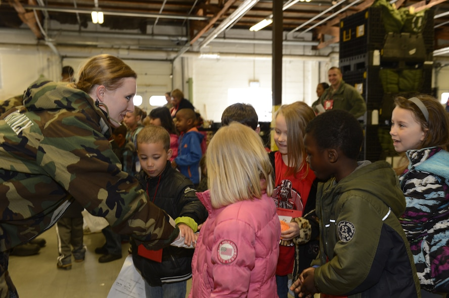 Students from Bitburg and Spangdahlem Elementary Schools gain firsthand experience of the mission oriented protective posture gear worn by U.S. Air Force Senior Airman Sarah Dumas, 52nd Logistics Readiness Squadron, central storage technician from Bowling Green, Ohio, during Kids' Deployment Day April 15, 2014, at Spangdahlem Air Base, Germany. Airmen allowed students to feel and try on military protective gear during the event. (U.S. Air Force photo by Staff Sgt. Christopher Ruano/Released)