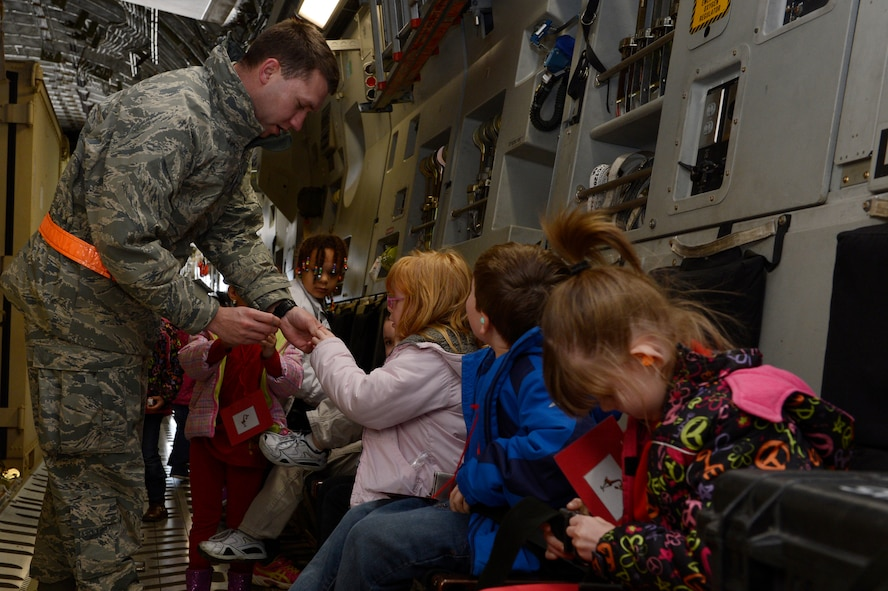 U.S. Air Force Senior Airman Nathan Stephenson, 726th Air Mobility Squadron controller from Bryson, Texas, buckles in children during Kids' Deployment Day April 15, 2014, at Spangdahlem Air Base, Germany. Base organizers held the event for students from the Bitburg and Spangdahlem Elementary Schools. (U.S. Air Force photo by Staff Sgt. Christopher Ruano/Released)