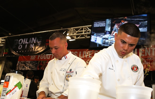 Gunnery Sgt. Justin Bell and Sgt. Arturo Torres cook during the Boiling Points competition held at the Del Mar Fairgrounds April 16. Boiling Points is a competition hosted by Aaron Williams, the corporate division chef for Food Fanatics, Los Angeles. The competition challenged the Marine Corps, Army, Navy and Coast Guard to go head-to-head in a 45-minute cooking competition. The Marine team took 1st place with their dish of an appetizer of fried eggplant and seared scallop caprese, and an entrée of seared duck, sweet potatoes and a fruit medley with a star fruit and horn melon sauce. Bell is the enlisted aide for the Marine Corps Recruit Depot's commanding general and Torres is the chief cook for the 62 Area Mess hall on Camp Pendleton.