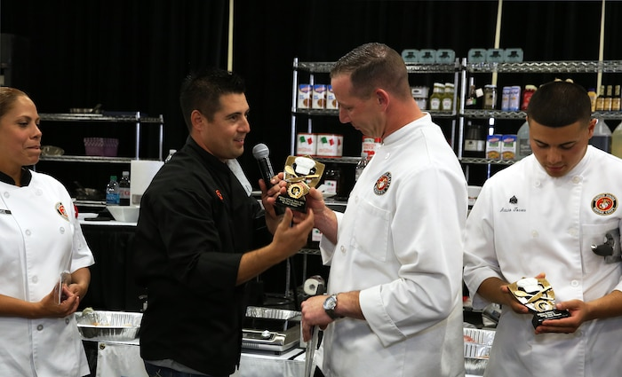Aaron Williams presents Gunnery Sgt. Matthew Jacobs with the 1st place trophy during the Boiling Points competition held at the Del Mar Fairgrounds April 16. Boiling Points is a competition hosted by Aaron Williams, the corporate division chef for Food Fanatics, Los Angeles. The competition challenged the Marine Corps, Army, Navy and Coast Guard to go head-to-head in a 45-minute cooking competition. The Marine team took 1st place with their dish of an appetizer of fried eggplant and seared scallop caprese, and an entrée of seared duck, sweet potatoes and a fruit medley with a star fruit and horn melon sauce. Jacobs is the enlisted aid for the I Marine Expeditionary Force's commanding general.