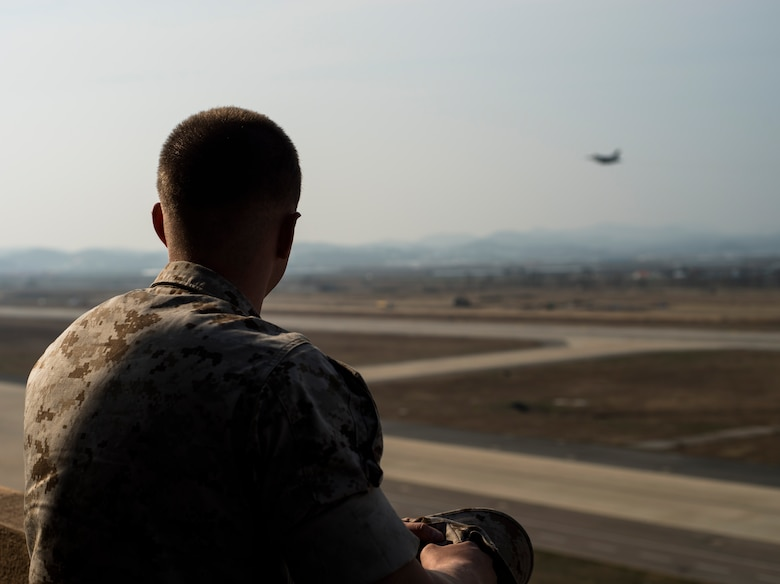 Marine Corps Cpl. Jake Balcom watches an F-16 take off March 26, 2014, at Osan Air Base, Republic of Korea. Balcom's grandfather, Col. Ralph Balcom, served as a fighter pilot in Vietnam, but has been missing in action since May 15, 1966. (U.S. Air Force photo by Staff Sgt. Jake Barreiro)