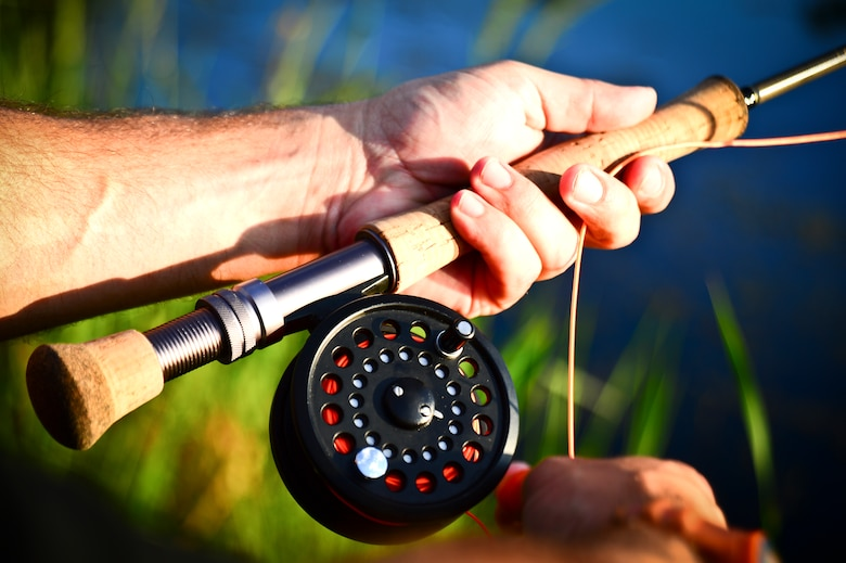 A participant from Project Healing Waters Fly Fishing  holds a rod and reel while waiting for a fish strike at MacDill Air Force Base, Fla., April 17, 2014.  The group's most recent outing took place at MacDill Air Force Base's Lewis Lake, where volunteers aided participants as they honed their new-found casting skills and dipped their freshly tied flies. (U.S. Air Force photo by Staff Sgt. Brandon Shapiro/Released)