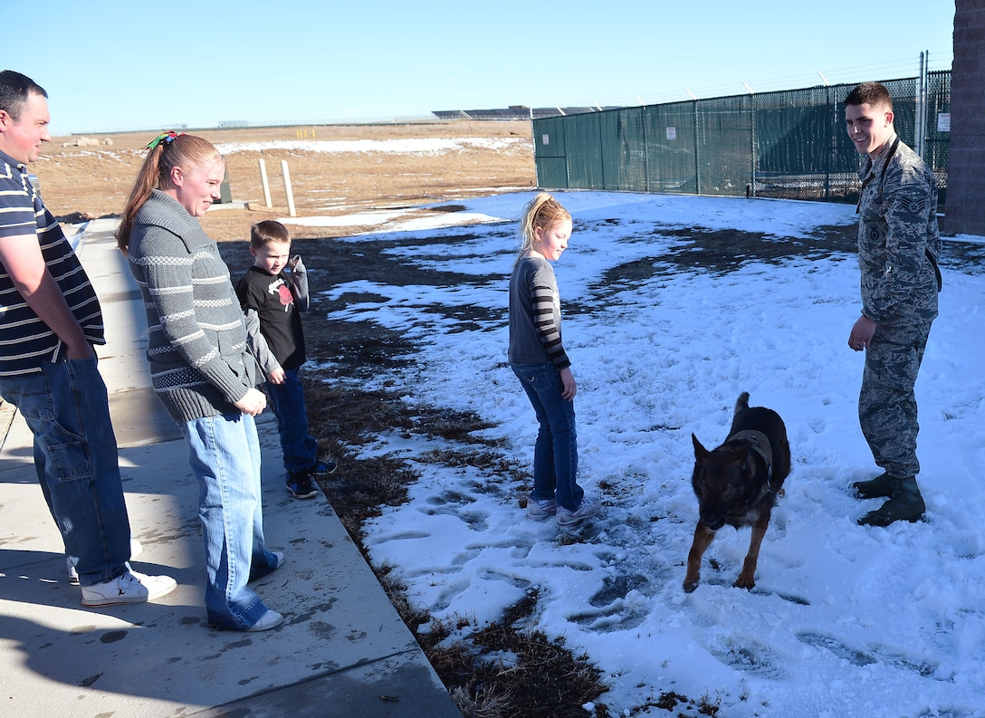 Staff Sgt. Jordan Gunterman, 460th Security Forces Squadron military working dog handler, right, and Nina, MWD, play with the Wulfers family Jan. 23, 2014, outside the 460th SFS kennels on Buckley Air Force Base, Colo. Gunterman was the first responder to a drunken driving car accident that affected the Wulfers family. (U.S. Air Force photo by Senior Airman Riley Johnson/Released)