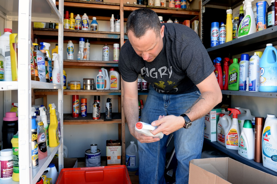 U.S. Air Force Master Sgt. Jared Ralphs, 372nd Training Squadron Detachment 17 F-16 Flying Falcon fighter aircraft crew chief instructor, organizes a box of household cleaning supplies into the chemical locker at the Spangdahlem Recycling Center at Spangdahlem Air Base, Germany, April 16, 2014. The chemical locker stands as a free service to DOD ID card holders to drop off or pick up any used bottled or canned materials such as spray paint, tire wax or cleaning supplies. (U.S. Air Force photo by Senior Airman Alexis Siekert/Released)