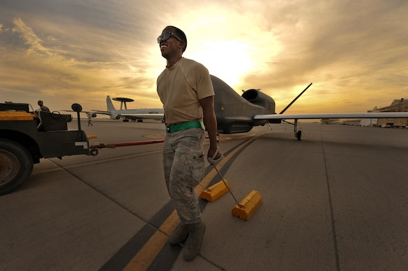 Senior Airman Arrelius Oliver drags the chocks for an RQ-4 Global Hawk April 15, 2014, in Southwest Asia. Arrelius, deployed from Beale Air Force Base, Calif., was part of a crew preparing the aircraft for a mission that evening. Oliver is a 380th Expeditionary Aircraft Maintenance Squadron assistant dedicated crew chief. (U.S. Air Force photo/Tech. Sgt. Russ Scalf)