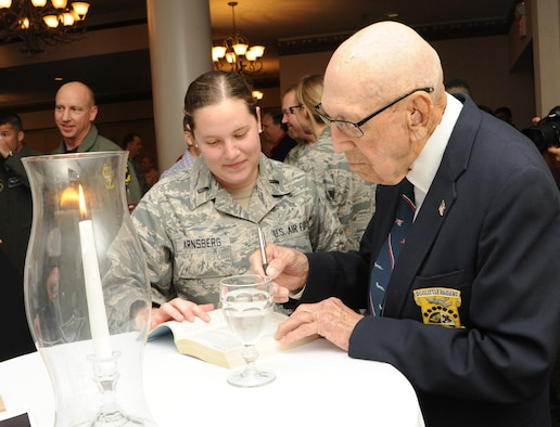 Retired Lt. Col. Richard Cole, co-pilot of Aircraft No. 1 from the Doolittle Tokyo Raid, signs an autograph for 1st Lt. Emily Arnsberg, from Joint Base San Antonio-Randolph, during the 72nd Doolittle Tokyo Raiders anniversary celebration event April 18 at the JBSA-Randolph Parr Club.  Cole is one of four remaining survivors from the Doolittle Tokyo Raid of 1942.  (U.S. Air Force photo/Melissa Peterson)