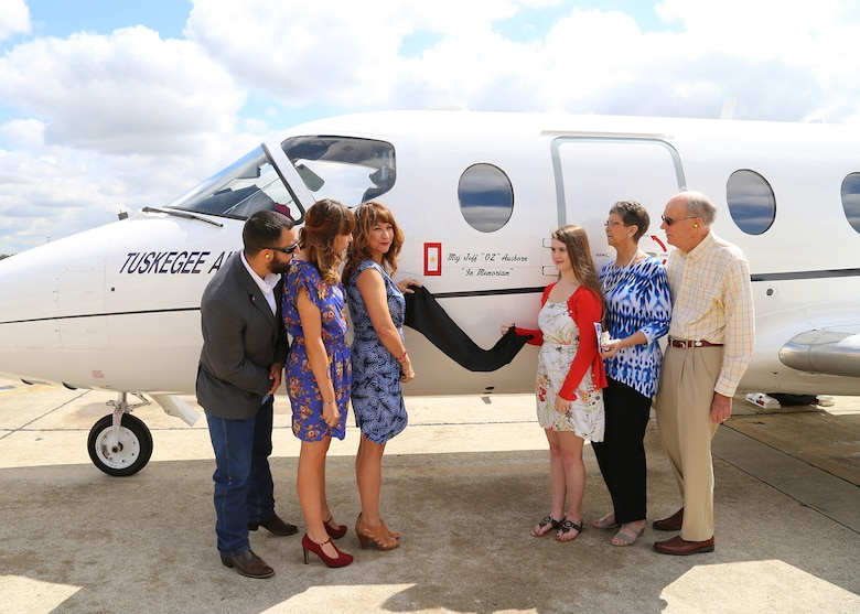 Maj. Jeff Ausborn's family unveils a special dedication painted on a T-1A aircraft in memory of Ausborn April 18 during a ceremony at Joint Base San Antonio-Randolph. Pictured (from left) are Mitchell Maloy, step-son, Summer Maloy, step-daughter, Suzanna Ausborn, widow, Emily Ausborn, daughter, and Faye and Clifford Ausborn, parents. Ausborn was deployed from JBSA-Randolph and killed April 27, 2011, in Kabul, Afghanistan, when a shooter opened fire at the Kabul International Airport killing eight Airmen and one American contractor.  Ausborn was a senior pilot, having logged more than 2,300 hours in airlift and trainer aircraft to include the T-37B, T-44, C-130E, T-6A, T-1A and C-27. (U.S. Air Force photo by Melissa Peterson)