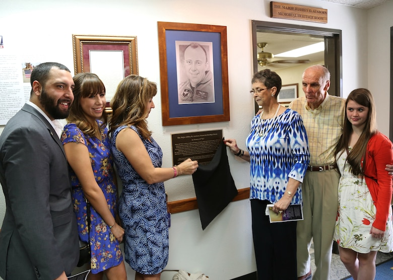 Family members of Maj. Jeff Ausborn unveil the Maj. Jeffrey Ausborn Memorial Heritage Room plaque April 18 at the 99th Flying Training Squadron at Joint Base San Antonio-Randolph.  Pictured (from left) are Mitchell Maloy, step-son, Summer Maloy, step-daughter, Suzanna Ausborn, widow, Faye and Clifford Ausborn, parents, and Emily Ausborn, daughter. Ausborn, 41, was deployed from JBSA-Randolph and killed April 27, 2011, in Kabul, Afghanistan, when a shooter opened fire at the Kabul International Airport killing eight Airmen and one American contractor.  Ausborn was deployed to the 438th Air Expeditionary Wing where he served as a C-27 instructor pilot to new Afghan pilots. (U.S. Air Force photo by Melissa Peterson)
