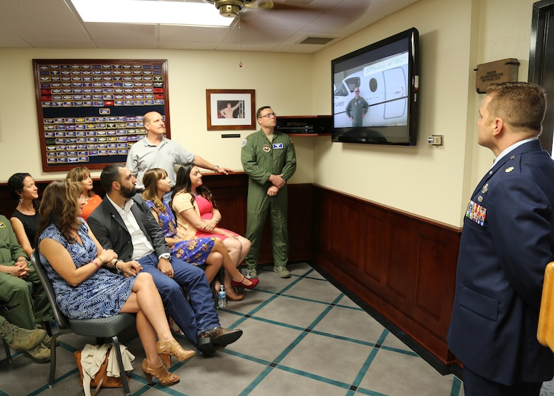 Maj. Jeff Ausborn's family and friends watch a slide show in the Ausborn Memorial Heritage Room during a dedication ceremony April 18 at the 99th Flying Training Squadron at Joint Base San Antonio-Randolph.  Ausborn was deployed from JBSA-Randolph and killed April 27, 2011, in Kabul, Afghanistan, when a shooter opened fire at the Kabul International Airport killing eight Airmen and one American contractor. (U.S. Air Force photo by Melissa Peterson)