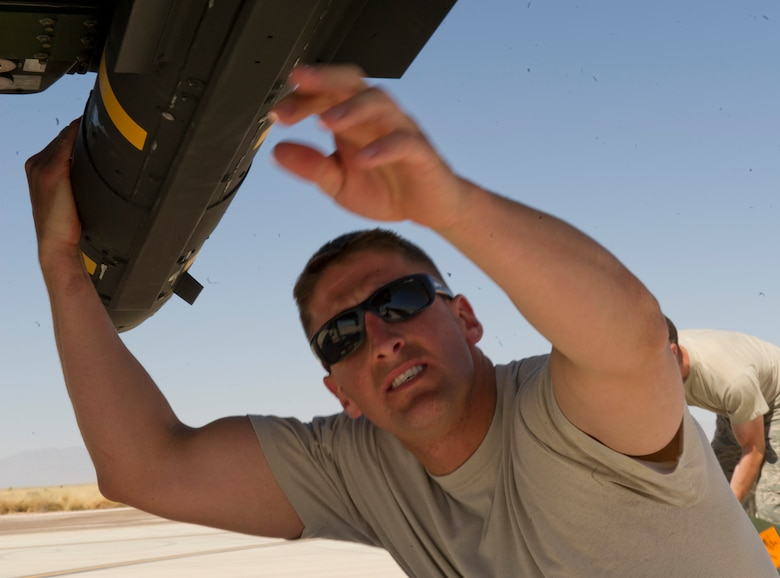 Staff Sgt. Aaron Updike, a weapons load crew chief from the 849th Aircraft Maintenance Squadron, completes a post munitions loading inspection on the Air-to-Ground Missle-114 Hellfire at Holloman Air Force Base, N.M., April 16. Updike was a part of a training exercise where the MQ-9 Reaper was loaded with live ammunitions in preparation for real world missions. (U.S. Air Force photo by Staff Sgt. E'Lysia Wray/Released)