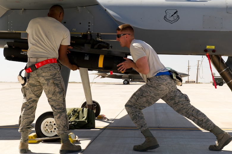 Airman 1st Class Ray Francis, a weapons load crew member from the 849th Aircraft Maintenance Squadron and Staff Sgt. Aaron Updike, a weapons load crew chief from the 849th AMXS, complete a munitions loading operation on the MQ-9 Reaper with Air-to-Ground Missle-114 Hellfires at Holloman Air Force Base, N.M., April 16. The airmen were a part of a training exercise where the MQ-9 Reaper was loaded with live ammunitions in preparation for real world applications. (U.S. Air Force photo by Staff Sgt. E'Lysia Wray/Released)