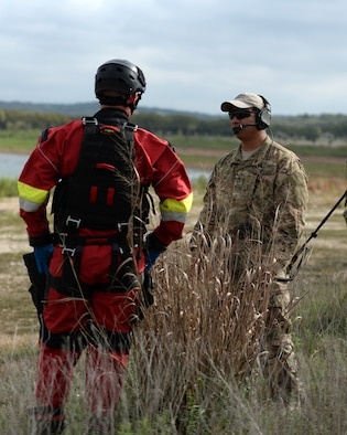 A tactical air control party member from the 147th Air Support Operations Squadron, 147th Reconnaissance Wing, based at Ellington Field Joint Reserve Base in Houston, Texas, discusses the search and rescue mission with a member from the Federal Emergency Management Agency's Texas Task Force 1 during a search and rescue exercise at Canyon Lake, Texas, April 11, 2014. The joint, interagency exercise simulated emergency response following a hurricane, with members from the Texas Air National Guard, Texas Army National Guard, Texas Task Force 1, the U.S. Coast Guard and Texas Department of Public Safety integrating to form a joint response team.