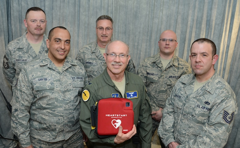 Senior Master Sgt. Curt Robichaud, avionics section supervisor with the 103rd Maintenance Squadron, Chief Master Sgt. Greg Boswell, the component maintenance chief with the 103rd Maintenance Squadron, Master Sgt. Jonathan Shepard, aircraft fuel systems specialist with the 103rd Maintenance Squadron, Tech. Sgt. Angel Santos, machine shop supervisor with the 103rd Maintenance Squadron, Col. James Galloway, commander of the 103rd Medical Group and Tech. Sgt. Anthony Gagliardi Jr., a budget analyst with the 103rd Maintenance Group proudly display an automated external defibrillator at Bradley Air National Guard Base, East Granby, Conn., April 6, 2014.  The team is credited with saving the life of Chief Master Sgt. Kevin Salsbury, a labor relations specialist with the Connecticut National Guard, using an AED like the one show just two days earlier here.  (U.S. Air National Guard photo by Master Sgt. Erin McNamara)