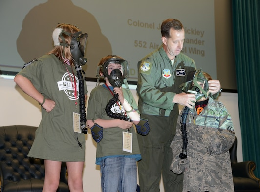 """Col. Jay Bickley, 552nd Air Control Wing commander, helps some Operation K.U.D.O.S. attendees adjust their """"warrior"""" masks during their briefing before they deployed to Camp Courage April 12. Children reported for duty at their designated chalk times to go through the personnel deployment function line, where they received their deployment supplies, then were briefed by base leaders, who explained how deployments work. (Air Force photo by Kelly White)"""