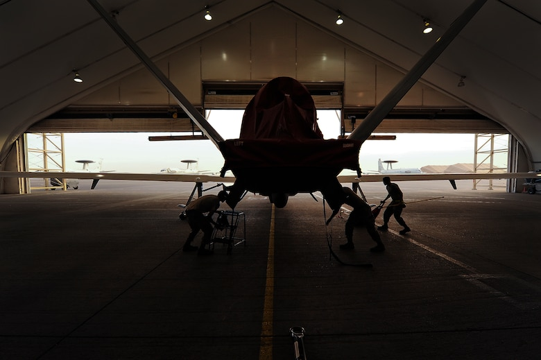 Airmen from the 380th Expeditionary Aircraft Maintenance Squadron prepare an RQ-4 Global Hawk for a flight April 15, 2014, at an undisclosed location in Southwest Asia. The Global Hawk is an unmanned aircraft that provides intelligence, surveillance, reconnaissance and communications capabilities over Southwest Asia. (U.S. Air Force photo by Tech. Sgt. Russ Scalf/Released)