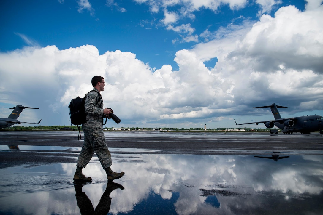 Senior Airman Dennis Sloan walks on the flightline in search of a photo May 5, 2013 at Joint Base Charleston, S.C. A victim of sexual assault, Sloan says his passion for photography keeps him breathing and offers solace from his otherwise painful memories. Sloan is a 628th Air Base Wing Public Affairs photojournalist. (U.S. Air Force photo/ Senior Airman George Goslin)