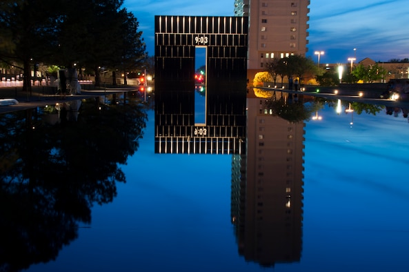 The sun sets on the Oklahoma City Memorial site.  One of the Gates of Time lights up to reveal the moment just after the Alfred P. Murrah Federal Building was bombed.  The site of the Reflecting Pool leading west toward this gate was once N.W. 5th St., with the Murrah Building just to the left.  (U.S. Air Force photo/Senior Airman Mark Hybers)