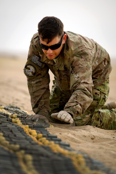 Staff Sgt. Paul Orosz, an explosive ordnance disposal technician, carefully arranges munitions slated for disposal at an undisclosed location in Southwest Asia.  Orosz is deployed to the 386th Expeditionary Civil Engineer Squadron from the 52nd CES at Spangdahlem Air Base, Germany. (U.S. Air Force photo by Senior Master Sgt. Burke Baker)(This image was manipulated for security purposes)