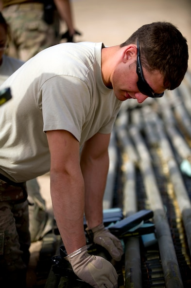 Airman 1st Class Keith Bochert, an explosive ordnance disposal technician from Patrick Air Force Base, Fla., carefully arranges munitions slated for disposal at an undisclosed location in Southwest Asia.  Bochert is deployed to the 386th Expeditionary Civil Engineer Squadron. (U.S. Air Force photo by Senior Master Sgt. Burke Baker)(This image was manipulated for security purposes)