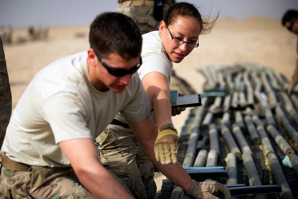Tech. Sgt. Angela Olguin, an explosive ordnance disposal technician, instructs Airman 1st Class Keith Bochert on properly placing explosive charges on munitions slated for disposal at an undisclosed location in Southwest Asia.  The two EOD Airmen have been deployed to the 386th Expeditionary Civil Engineer Squadron since mid-January. (U.S. Air Force photo by Senior Master Sgt. Burke Baker)
