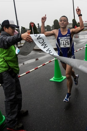 Nobuhisa Tanigawa, a participant of the 2014 Kintai Marathon, which took place aboard Marine Corps Air Station Iwakuni, Japan, runs through finish line tape after completing a marathon, April 13. The Kintai Marathon is one of the few annual events that give Japanese citizens an opportunity to come aboard station. Approximately 800 people signed up for the full marathon, half marathon and five-kilometer walk.
