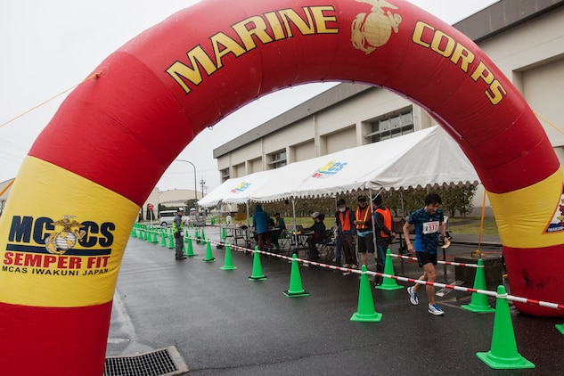A Japanese participant of the 2014 Kintai Marathon, which took place aboard Marine Corps Air Station Iwakuni, Japan, runs past the finish line, April 13. The Kintai Marathon is one of the few annual events that give Japanese citizens an opportunity to come aboard station. Approximately 800 people signed up for the full marathon, half marathon and five-kilometer walk.