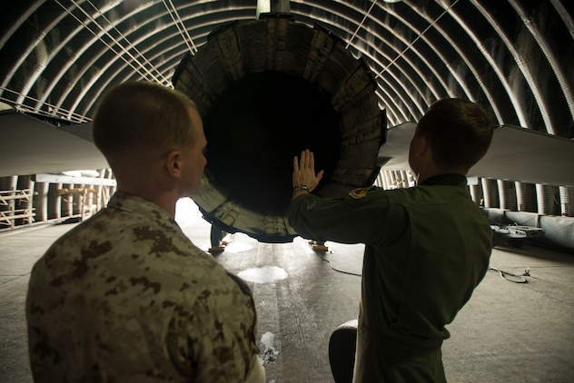 Marine Corps Cpl. Jake Balcom is shown the exhaust end of an F-16 by Capt. Jay Doerfler, 421st Fighter Squadron chief of training, March 26, 2014, at Osan Air Base, Ark. Balcom spent two days touring his grandfather's old squadron, the 421st FS, which was deployed to Osan AB from Hill Air Force Base, Utah. (U.S. Air Force photo by Staff Sgt. Jake Barreiro)