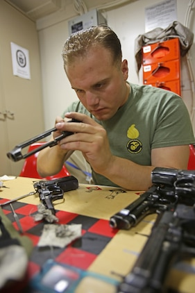Corporal Michael Yodice inspects and cleans M9 service pistols aboard amphibious transport dock ship USS Anchorage (LPD 23). Yodice is from Butler, N.J., and the sole Marine Corps armorer aboard the ship. As a small arms repair technician with 1st Maintenance Battalion, 1st Marine Logistics Group, he was responsible for making sure the different weapons systems worked for the nearly 200 Marines and sailors with his current