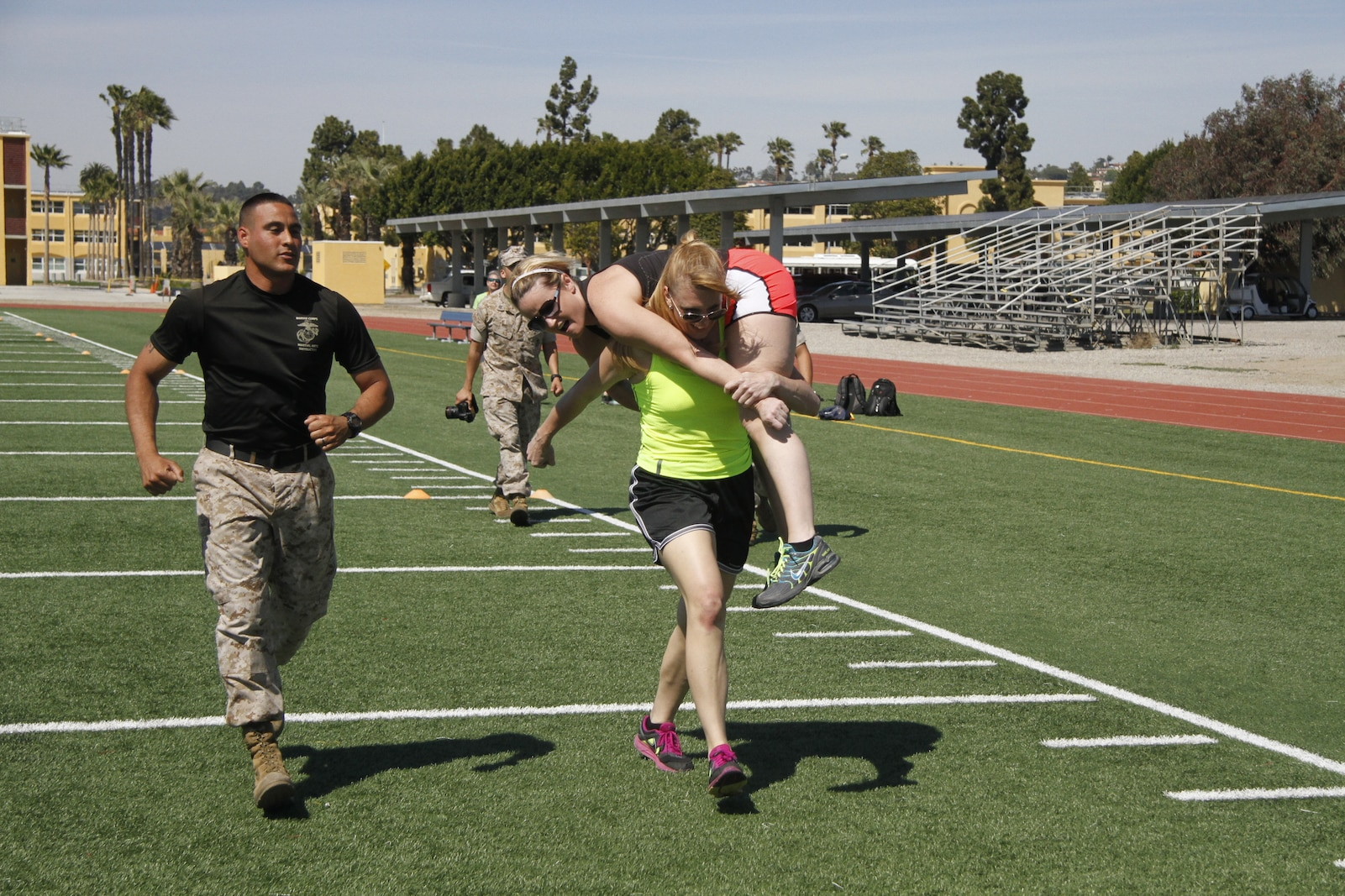Liane R. Hager, a Harrisonville High School family and consumer sciences teacher, carries Jenny R. Bruns, a Harrisonville High School art teacher, as part of a mock Combat Fitness Test during the Educators' Workshop at Marine Corps Recruit Depot San Diego April 8, 2014. Educators from both Recruiting Station Kansas City and Lansing took part in the workshop. The workshop included the educators asking questions about the rigors of recruit training, firing the M16A4 assault rifle, amongst many other aspects of recruit training.