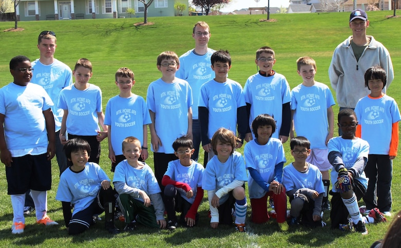 """The Mountain Home Air Force Base Youth Center-sponsored """"Thunderbolts,"""" team poses for a photo after their soccer game at Legacy Park in Mountain Home town, April 19, 2014. The team consists of: Brayden Shields, Davis Saunders, Matthew Johnson, Kell Iverson, Liam Wallace, Ethan Ferguson, Casey Sitton, Enzo Yeo, Hagen Flahaut, Donovan Gordon, Eason and Elton Li, Donte Brazell, Kalib Ferguson, and Cyrus and Skylar Tham. The team is coached by Airman 1st Class Zachary McGrew, 366th Comptroller Squadron, Airman 1st Class John Eckart, 726th Air Control Squadron. and Lt. Col. Jeremy Saunders, 366th Aircraft Maintenance Squadron commander. (Courtesy photo)"""