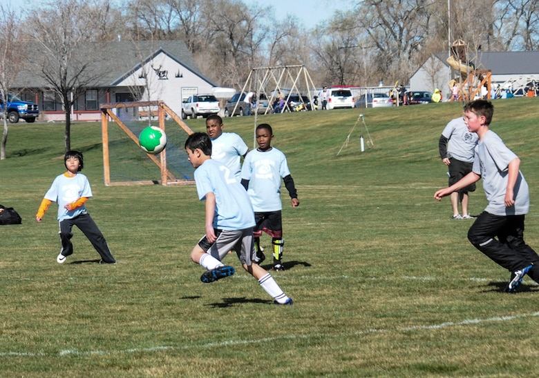 Liam Wallace, Mountain Home Air Force Base Youth Center's Thunderbolts soccer team center midfielder, leans forward to head the ball to Cyrus Tham, right striker, as teammates look on and a defender moves in to stop the attack at Legacy Park in Mountain Home town, Idaho, April 19, 2014. Diversity plays a large role in the team line-up, which consists of 16 children, six of whom are children of Republic of Singapore Airmen. Cyrus Tham and his twin-brother Skylar are two RSAF children. The RSAF live among U.S. Air Force and in the local community, and train at the 428th Fighter Squadron, as part of the Peace Carvin V program, a long-term partnership between the USAF and RSAF. (U.S. Air Force photo by Master Sgt. Kevin Wallace/RELEASED)