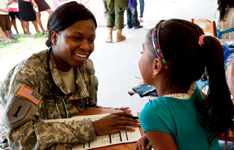 U.S. Army Sgt. Karen Burbank, medic, left, talks with a Belizean girl while checking her in for medical care April 7, 2014, at the Chunox Roman Catholic Pre-School in Chunox, Belize. Burbank, a Belize City native, is deployed from the 349th Combat Support Hospital, a Reserve unit in Los Angelas, Calif. The care was provided as part of a medical training exercise, or MEDRETE, that offers U.S. and Canadian military doctors and nurses the opportunity to train and interact with their Belizean counterparts. Free care will also be available 9 a.m. to 4 p.m. April 14-17 at the Libertad Methodist School. (U.S. Air Force photo by Tech. Sgt. Kali L. Gradishar/Released)