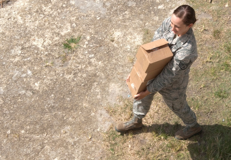 U.S. Air Force Staff Sgt. Molly Cox, New Horizons medical logistics, carries a box of while packing up operations at the school on the final day of the medical readiness training exercises April 17, 2014, in Libertad, Belize. The exercises, also known as MEDRETES, offered U.S. and Canadian military doctors and nurses the opportunity to train and interact with their Belizean counterparts while providing free health care to Belizean residents. (U.S. Air Force photo by Tech. Sgt. Kali L. Gradishar/Released)
