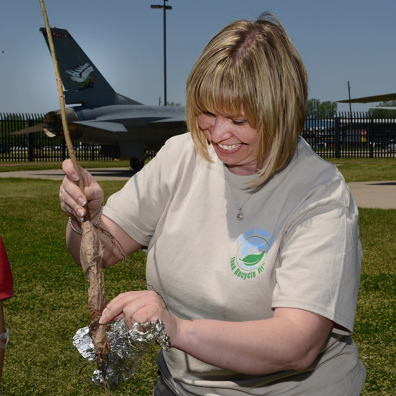 Angel Adams, 138th Fighter Wing Environmental Management Office, assists in planting trees at an Earth Day celebration at the 138th Fighter Wing, 22 April 2014.  The 138th FW EMO organized a cookout and other green activities to celebrate the day at the Tulsa Air National Guard base, Tulsa Okla.  (U.S. National Guard photo by Senior Master Sgt.  Preston L. Chasteen/Released)
