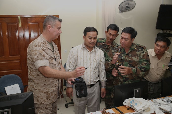 """U.S. Navy Cmdr. Alberto Fernandez-Milo, left, shows Cambodia military medical personnel how to use an """"ear, nose and throat"""" kit during a practical application seminar March 20 as part of Cambodia Medical Exercise 14-1 in Phnom Penh, Cambodia. The seminar is part of a weeklong medical subject-matter expert exchange focused on preparing and planning for humanitarian assistance and disaster relief efforts. During the seminar, participants learned how to properly use and improvise certain medical equipment, such as tourniquets, to better support first aid and triage procedures. Fernandez-Milo is a psychiatrist with 4th Medical Battalion, 4th Marine Logistics Group, U.S. Marine Corps Forces Reserve."""