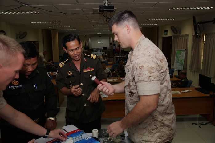 U.S. Navy Petty Officer 2nd Class Ryan W. Marczynski, right, shows an intraosseous catheter to Royal Cambodian Army Col. Mey Thun Nara  during a practical application seminar March 20 as part of Cambodia Medical Exercise 14-1 in Phnom Penh, Cambodia. The catheter is used to initiate fluid resuscitation. The seminar is part of a weeklong medical subject-matter expert exchange focused on preparing and planning for humanitarian assistance and disaster relief efforts. During the seminar, participants learned how to properly use and improvise certain medical equipment, such as tourniquets, to better support first aid and triage procedures. Nara is a pharmacist and the deputy director of the Cambodia Ministry of Health. Marczynski is a corpsman with 3rd Medical