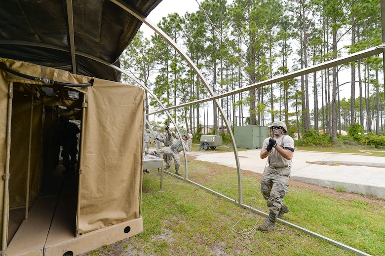U.S. Air Force Staff Sgt. Jerry Vincent, water and fuel systems maintenance specialist with the 116th Civil Engineering Squadron (CES), Georgia Air National Guard (ANG), Robins Air Force Base, Ga., pulls the outer cover over a tent while erecting a shelter at Silver Flag training at Tyndall Air Force Base, Fla., April 17, 2014. During the weeklong course, Guardsmen from the 116th CES along with 219 Airmen from multiple U.S. Air Force active duty, Reserve and ANG units trained on building and maintaining bare-base operations at a simulated forward-deployed location. In addition, they honed their combat and survival skills, repaired simulated bomb-damaged runways, practiced EOD scenarios, set up base facilities and established various critical base operating support capabilities. Thirty-four Airmen from the 116th CES attended the exercise that consisted of extensive classroom and hands-on training culminating in an evaluation of learned skills on the last day of class. (U.S. Air National Guard photo by Master Sgt. Roger Parsons/Released)