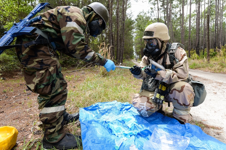 U.S. Air Force Staff Sgt. Edgar Mullinax, right, emergency management specialist with the 116th Civil Engineering Squadron (CES), Georgia Air National Guard (ANG), Robins Air Force Base, Ga., and Staff Sgt. Im Southavout, emergency management specialist with the 5th CES, Minot Air Force Base, N.D., test vegetation for radiological contamination at Silver Flag training at Tyndall Air Force Base, Fla., April 17, 2014. During the weeklong course, Guardsmen from the 116th CES along with 219 Airmen from multiple U.S. Air Force active duty, Reserve and Air National Guard units trained on building and maintaining bare-base operations at a simulated forward-deployed location. In addition, they honed their combat and survival skills, repaired simulated bomb-damaged runways, practiced EOD scenarios, set up base facilities and established various critical base operating support capabilities. Thirty-four Airmen from the 116th CES attended the exercise that consisted of extensive classroom and hands-on training culminating in an evaluation of learned skills on the last day of class. (U.S. Air National Guard photo by Master Sgt. Roger Parsons/Released)