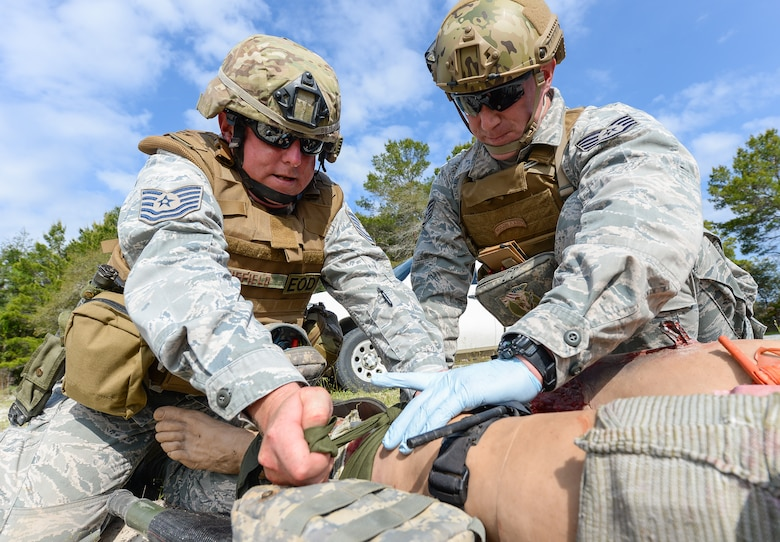 U.S. Air Force Tech. Sgt. Barry Duffield, left, an explosive ordnance disposal (EOD) technician with the 116th Civil Engineering Squadron (CES), Georgia Air National Guard (ANG), Robins Air Force Base, Ga., and Tech. Sgt. Dustin Turner, an EOD technician with the 123rd Airlift Wing, Kentucky ANG, Louisville, Ky., attempt to stop bleeding from the leg of a Multiple Amputation Trauma Trainer during Silver Flag training at Tyndall Air Force Base, Fla., April 17, 2014. During the weeklong course, Guardsmen from the 116th CES along with 219 Airmen from multiple U.S. Air Force active duty, Reserve and Air National Guard units trained on building and maintaining bare-base operations at a simulated forward-deployed location. In addition, they honed their combat and survival skills, repaired simulated bomb-damaged runways, practiced EOD scenarios, set up base facilities and established various critical base operating support capabilities. Thirty-four Airmen from the 116th CES attended the exercise that consisted of extensive classroom and hands-on training culminating in an evaluation of learned skills on the last day of class. (U.S. Air National Guard photo by Master Sgt. Roger Parsons/Released)