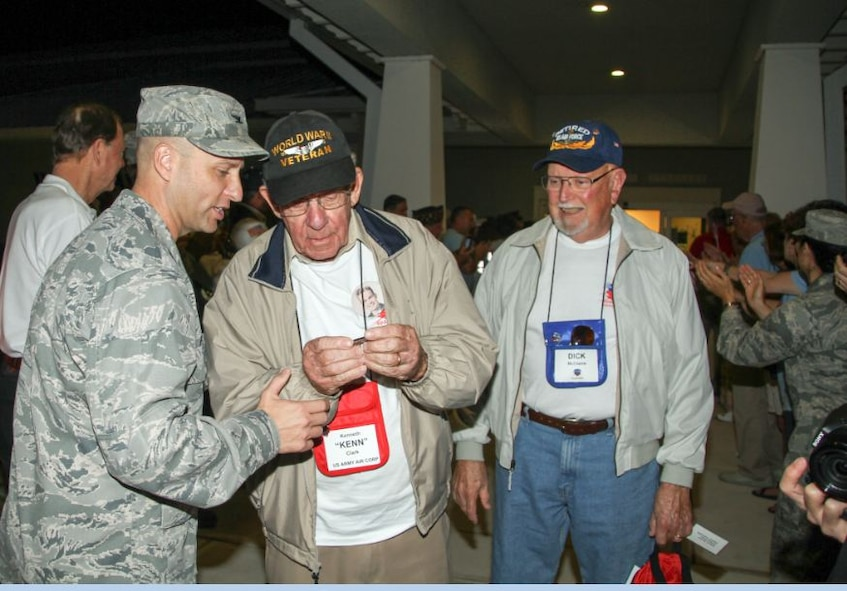 Col. Robert Pavelko, 45th Space Wing vice commander, gives an Honor Flight coin to retired U.S. Army Air Corps 1st Lt. Kenneth Clark, at the Honor Flight departure in Melbourne, Fla. April 12. Team Patrick-Cape volunteers were in attendance and met with World War II and Korean War veterans prior to flying to Washington D.C. to tour the U.S. Air Force Memorial, war memorials, and Arlington Cemetery, as part of the Honor Flight program. (Courtesy photo/Lou Seiler Jr.)
