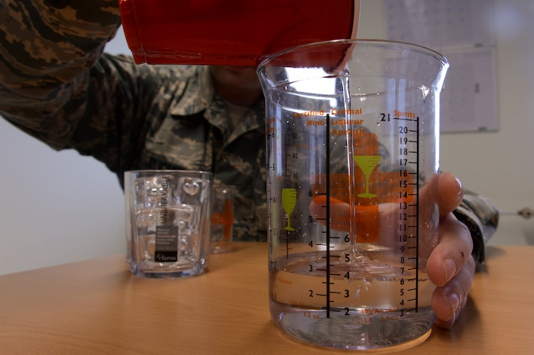 "U.S. Air Force Staff Sgt. Matthew Ruchie, a 52nd Medical Operations Squadron mental health craftsman, from St. Paul, Minn., pours water into a standard unit of measurement cup also referred to as a ""SUM–it-up cup,"" April 17, 2014, at Spangdahlem Air Base, Germany. A visual tool, the cup measures how much alcohol is used for the various types of drink sizes. (U.S. U.S. Air Force photo by Senior Airman Rusty Frank/Released)"
