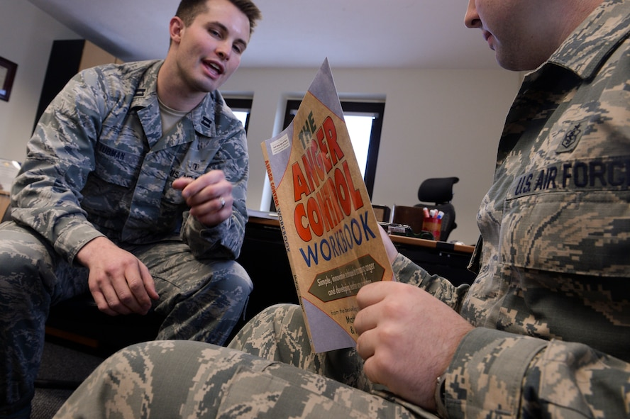 U.S. Air Force Capt. David Tubman, a 52nd Medical Operations Squadron clinical psychologist and the alcohol and drug prevention and treatment program manager from Napa, Calif., helps an Airman fill out a workbook April 17, 2014, at Spangdahlem Air Base, Germany. Members of the mental health services help Airmen stay mentally fit to accomplish the mission. (U.S. Air Force photo by Senior Airman Rusty Frank/Released)