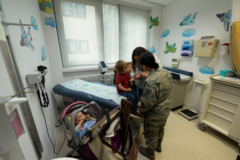 U.S. Air Force Tech. Sgt. Kelani Mendiola, 52nd Medical Operations Squadron non-commissioned-officer in charge of the pediatrics clinic from Guam, talks to a patient April 15, 2014, at Spangdahlem Air Base, Germany. Many flights fall under the 52nd MDOS including the pediatrics clinic. (U.S. Air Force photo by Senior Airman Rusty Frank/Released)