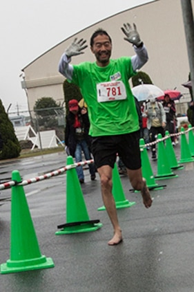 A Japanese participant of the 2014 Kintai Marathon, which took place aboard Marine Corps Air Station Iwakuni, Japan, runs barefoot toward the half-marathon finish line, April 13. The Kintai Marathon is one of the few annual events that give Japanese citizens an opportunity to come aboard station. Approximately 800 people signed up for the full marathon, half marathon and five-kilometer walk.